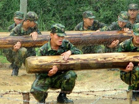 Chinese soldiers training by carrying logs