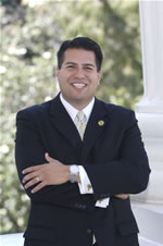 Assemblymember Felipe Fuentes in a suit smiling with arms crossed