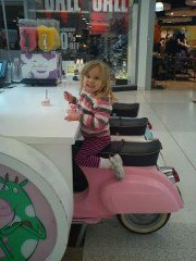 Four-year-old girl eating ice cream on a seat fashioned like a pink Vespa scooter