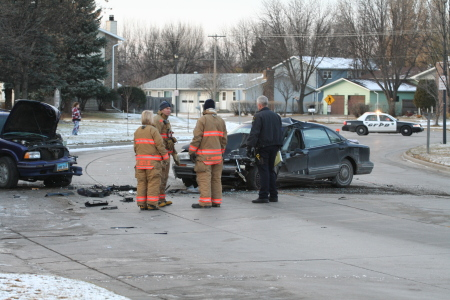 Car accident scene with firefighters and police officer standing nearby