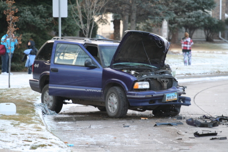 Blue GMC Jimmy SUV with hood open and severe damage to front driver side